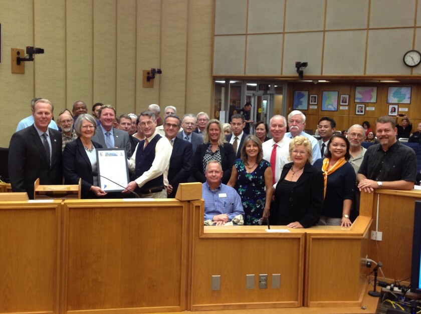 """Representatives from the more than 40 community planning groups across San Diego join San Diego Mayor Kevin Faulconer and City Council President Sherri Lightner (left, holding proclamation) in proclaiming Sept. 20, 2016, """"Community Planning Group 50th Anniversary Day."""""""