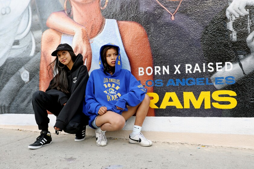 Alba Gabriela Hernandez, left, and Maya Salinas wear Born X Raised gear in front of a mural in East L.A.