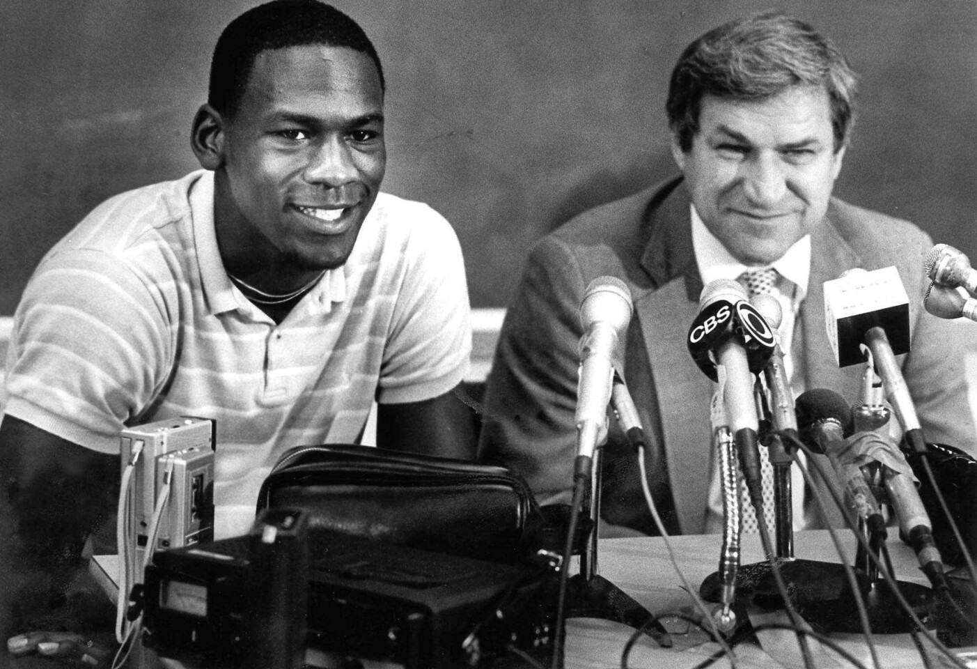 North Carolina guard Michael Jordan, left, and Tar Heels coach Dean Smith are shown at a news conference in Chapel Hill, N.C., where Jordan announced he would forfeit his final year of college eligibility to turn pro in 1984.