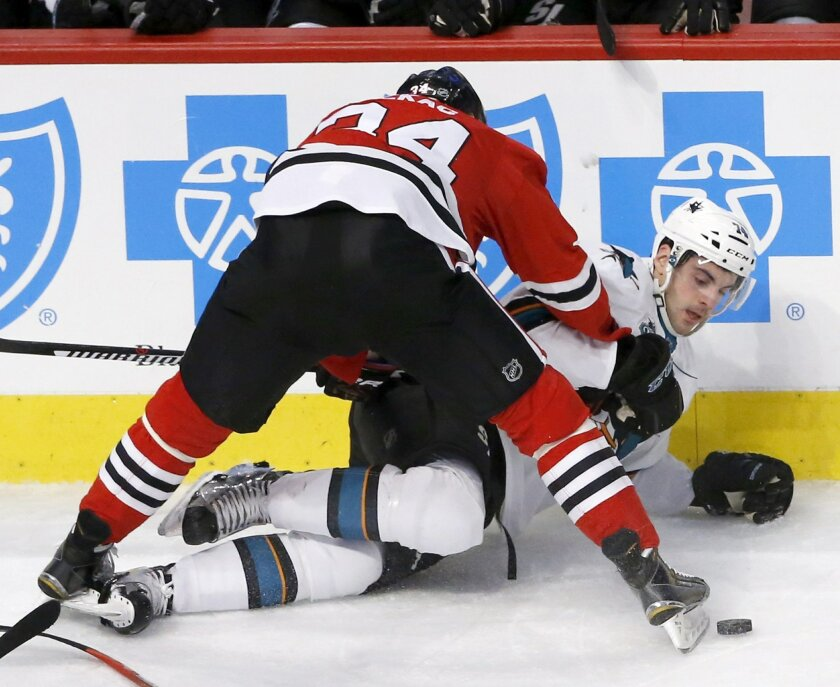 Chicago Blackhawks left wing Jiri Sekac (34) checks San Jose Sharks defenseman Dylan DeMelo to the ice during the first period of an NHL hockey game Tuesday, Feb. 9, 2016, in Chicago. (AP Photo/Charles Rex Arbogast)