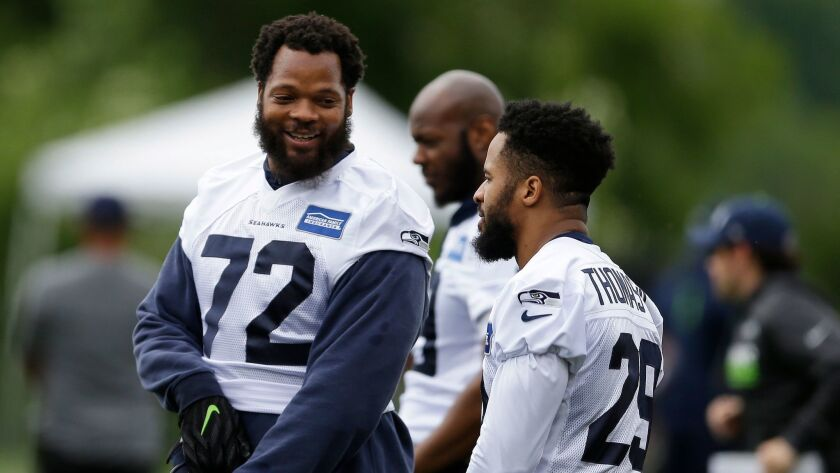 Seattle Seahawks defensive end Michael Bennett, above left at a recent football practice, is co-writ