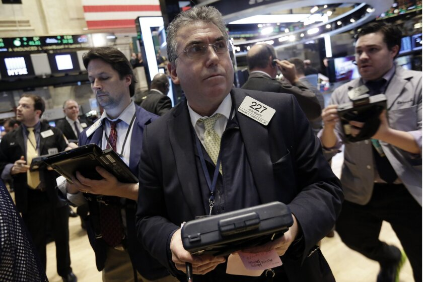 Trader John Bishop works on the floor of the New York Stock Exchange Thursday. A new poll says Americans see significant improvements in jobs and the market, but worry about the economy's vulnerability to another financial crisis.