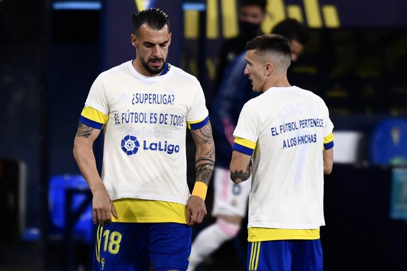 Álvaro Negredo (izquierda) y Salvi Sánchez, del Cádiz, visten camisetas con mensajes de protesta contra la Superliga europea, antes de su partido del miércoles 21 de abril de 2021, ante el Real Madrid (AP Foto/Jose Breton)