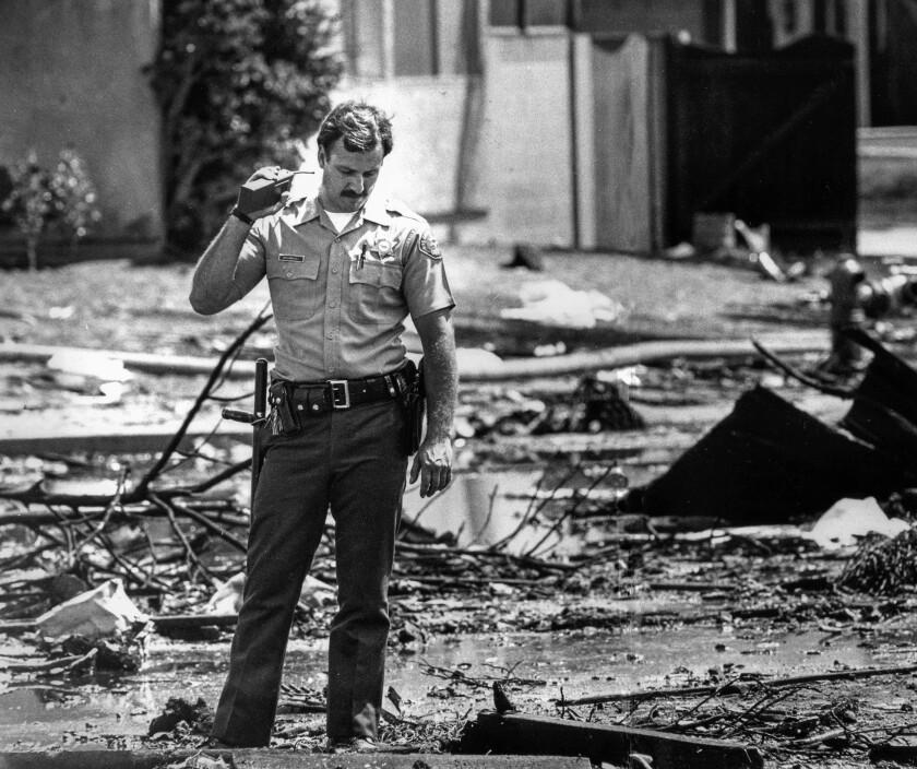 Aug. 31, 1986: A deputy stands amid debris on Holmes Avenue after the jetliner crash in Cerritos.