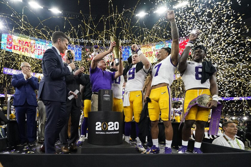 In this Jan. 13, 2020, photo, LSU coach Ed Orgeron holds the trophy after his team's national title game win over Clemson.