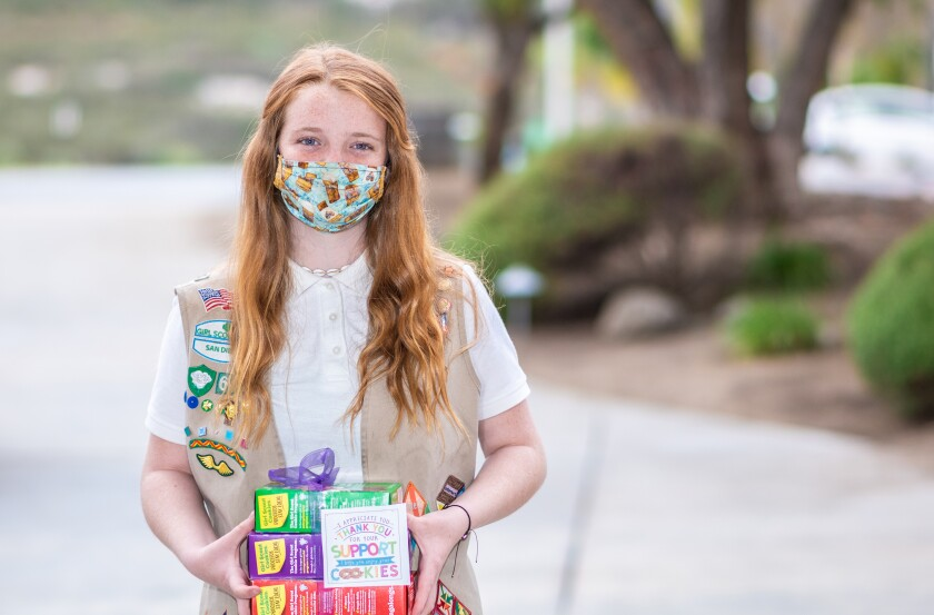 Brooklynn Johnson and other Ramona Girl Scouts are selling cookies in a socially distanced manner.