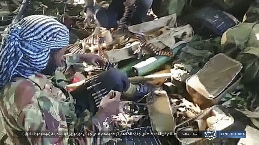 """This image distributed online by the Islamic State Central Africa Province (ISCAP) and provided by SITE Intelligence Group shows ISCAP fighters and weapons following clashes with Mozambican government troops on Thursday, Aug. 6, 2020, near Mocimboa da Praia, in northern Mozambique. The stinging success of Mozambique's Islamic extremist rebels in seizing and holding the northern port city signals to the government, neighboring countries and the world that Africa has yet another insurgency hotspot. Writing in Arabic reads """"Blessings of God are on the soldiers of the caliphate after their attack on the Mozambican army near the city of Mocimboa da Praia"""". (SITE Intelligence Group via AP)"""