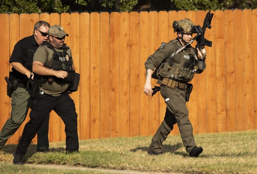 Police officers work near a house in Cedar Park, Texas