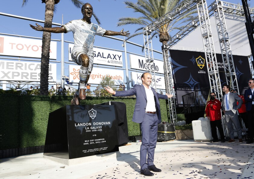Former Galaxy player Landon Donovan poses in front of his statue Sunday in Carson.