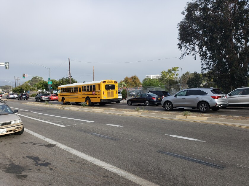 Vehicles — including a school bus — descend down Nautilus Street toward Muirlands Middle School at 8:15 Tuesday morning.