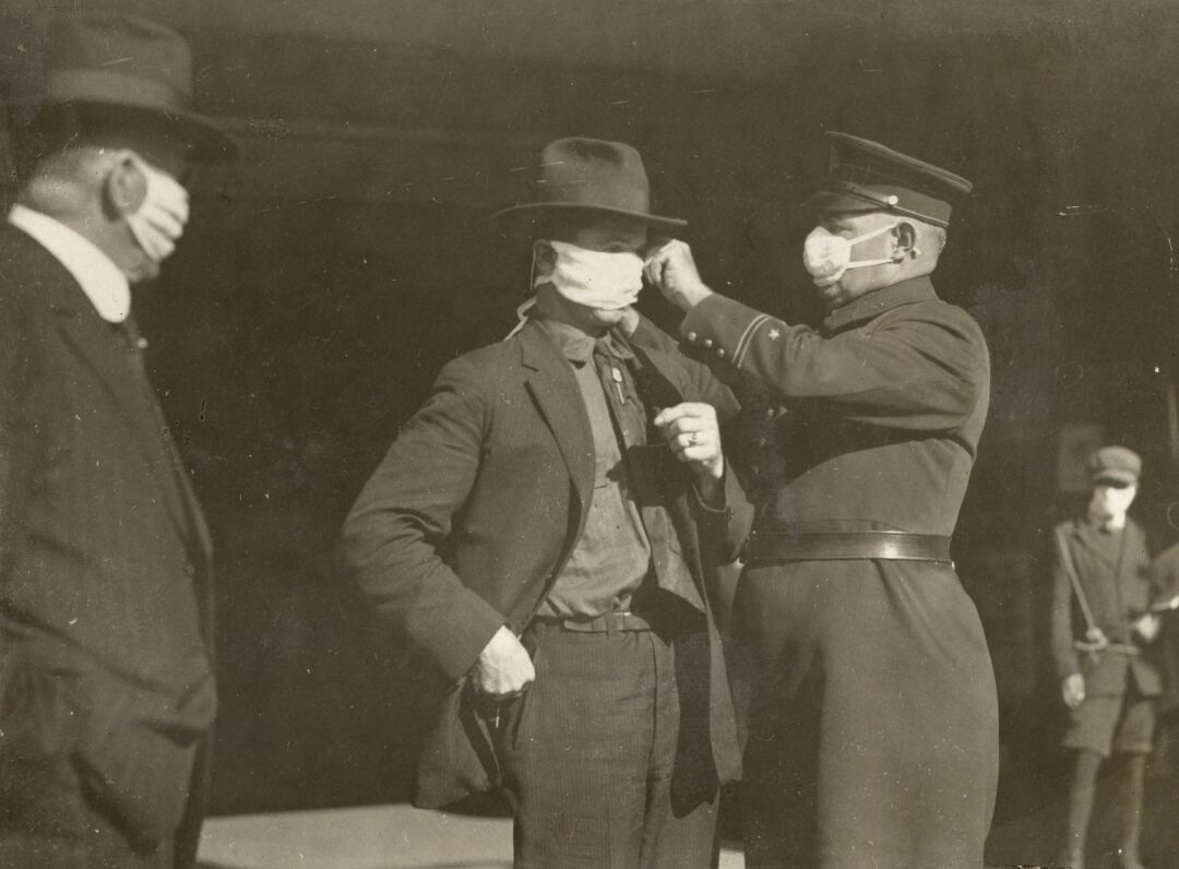 A police officer adjusts a man's flu mask in San Francisco during the 1918 pandemic.