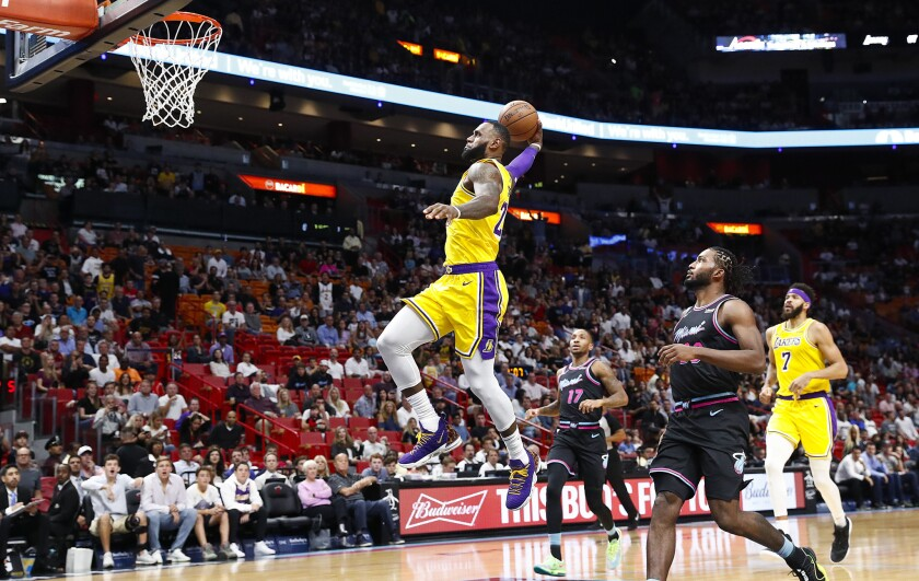 El alero de los Lakers de Los Ángeles LeBron James consigue una clavada en la primera mitad del juego ante el Heat de Miami el domingo 18 de noviembre de 2018 en Miami. (AP Foto/Brynn Anderson)