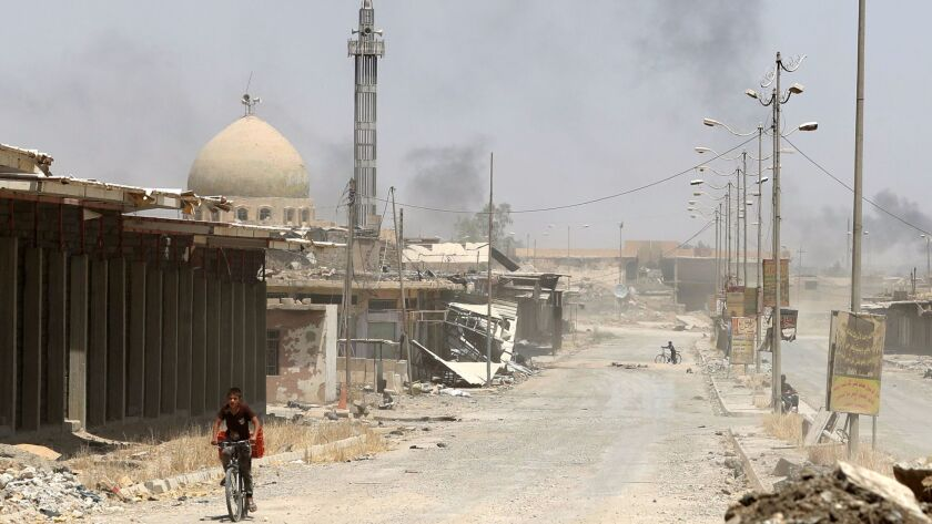 A boy rides a bicycle in west Mosul's Saha neighborhood on May 29, 2017, as smokes billows during ongoing battles between Iraqi forces and Islamic State militants.