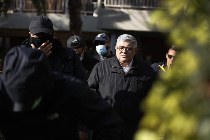 Golden Dawn party leader Nikos Michaloliakos, center, leaves his residence in Athens, Thursday, Oct. 22, 2020.A court has sentenced Michaloliakos and the leadership of Greece's extreme-right Golden Dawn party to 13 years in prison, imposing the near-maximum penalty for running a criminal organization blamed for numerous violent hate crimes. The landmark ruling follows a five-year trial of dozens of top officials, members, and supporters of the organization founded as a Neo-Nazi group in the 1980s, that rose to become Greece's third-largest political party during a major financial crisis in the previous decade. (AP Photo/Thanassis Stavrakis)