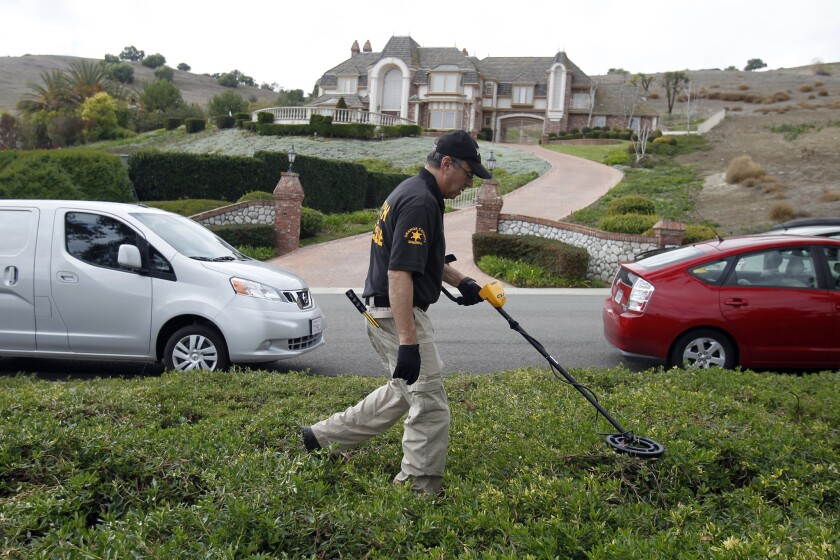 An Orange County sheriff's investigator examines property near the San Juan Capistrano cul-de-sac where Hans and Andra Sachs were killed. Their son, Ashton, pleaded guilty Tuesday to their murders.