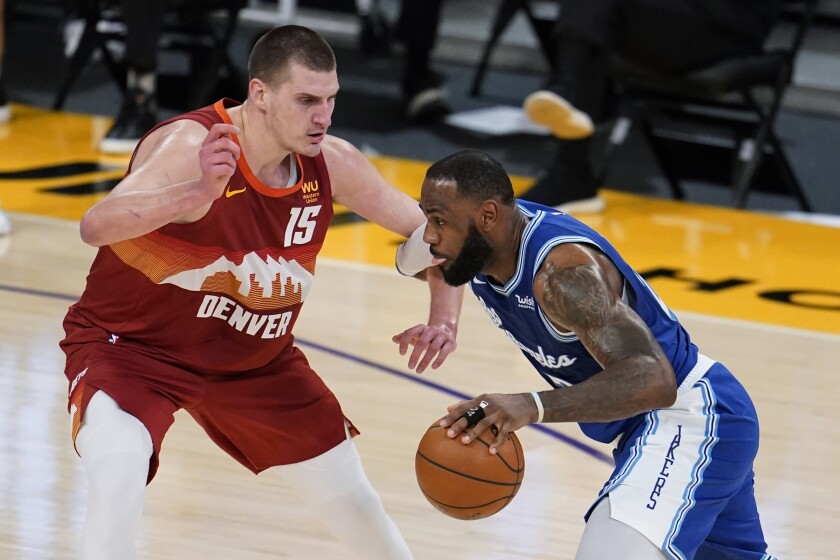 Los Angeles Lakers forward LeBron James, right, is defended by Denver Nuggets center Nikola Jokic (15) during the first half of an NBA basketball game Thursday, Feb. 4, 2021, in Los Angeles. (AP Photo/Marcio Jose Sanchez)