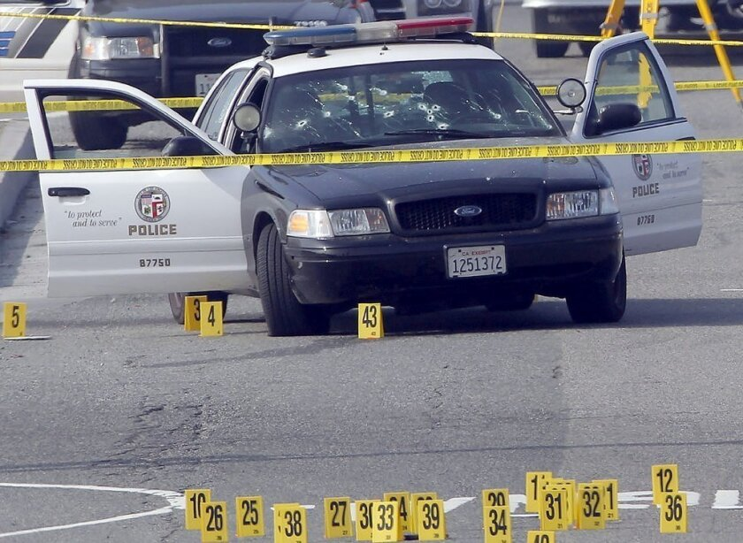 A bullet-damaged Los Angeles Police Department vehicle is taped off by police on Thursday in Corona. Former LAPD officer Christopher Dorner is suspected of shooting two officers who were sent to Corona to protect someone Dorner threatened.