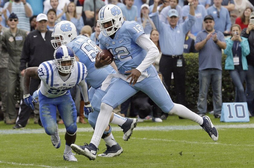 North Carolina quarterback Marquise Williams (12) scores a touchdown as Duke's DeVon Edwards (27) misses the tackle during the first half of an NCAA college football game in Chapel Hill, N.C., Saturday, Nov. 7, 2015. (AP Photo/Gerry Broome)