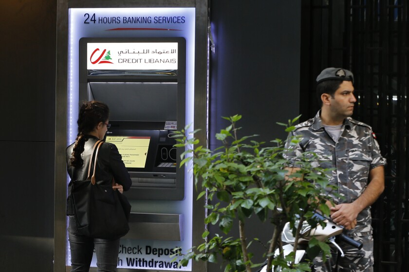 A woman uses ATM outside a bank, as a Lebanese policeman stands guard, in Beirut, Lebanon, Wednesday, Nov. 20, 2019. Lebanon's worsening financial crisis has thrown businesses and households into disarray. Banks are severely limiting withdrawals of hard currency, and Lebanese say they don't know how they'll pay everything from tuitions to insurance and loans all made in dollars. Politicians are paralyzed, struggling to form a new government in the face of tens of thousands of protesters in the streets for the past month demanding the entire leadership go. (AP Photo/Bilal Hussein)