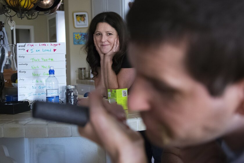 Karen Macbeth watches as her son Cheyne Johnston interacts with one of his professional caregivers.  Johnston who now lives with his mother suffered a traumatic brain injury last year in a off road motorcycle accident.