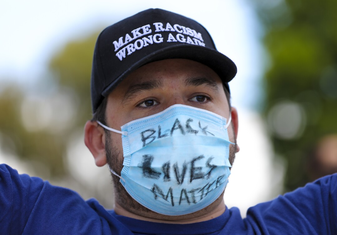 "Ryan Darsey wears a facial mask with the marking ""Black Lives Matters."" Darsey was among the group of protestors on Saturday who began their protest in front of La Mesa Police Department."