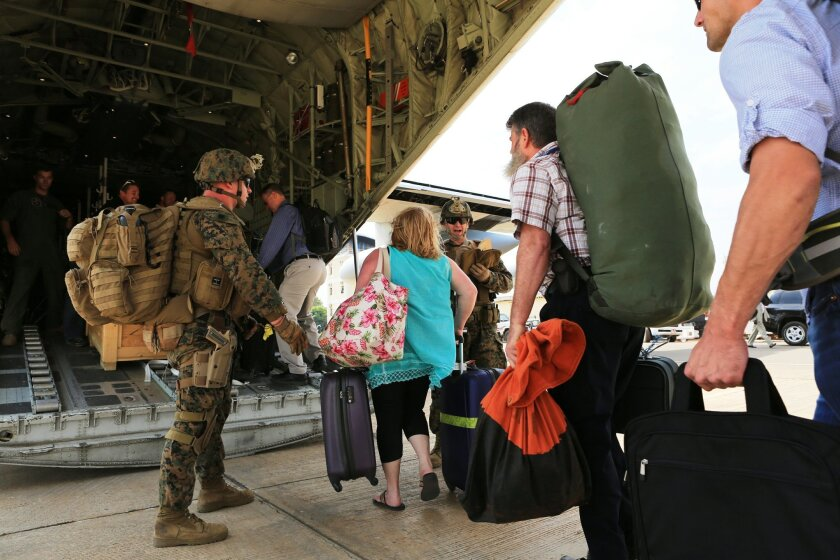 Marines and sailors with Special-Purpose Marine Air-Ground Task Force Crisis Response help U.S. citizens into a Marine Corps KC-130J Hercules airplane in Juba, South Sudan, during an evacuation of personnel from the U.S. Embassy.