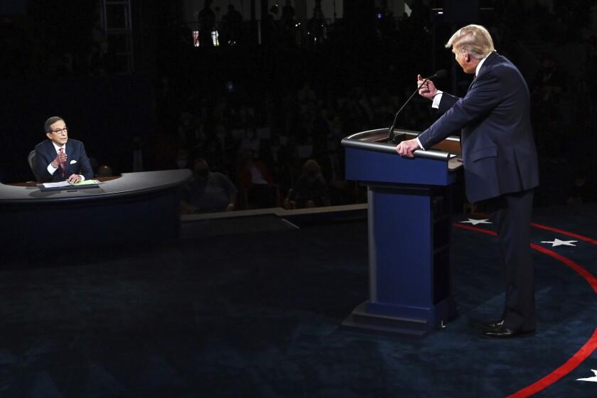 Donald Trump (der) discute con el moderador Chris Wallace durante el primer debate presidencial
