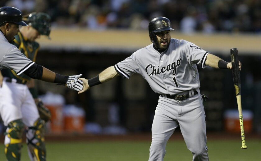 Chicago White Sox's Adam Eaton, right, is congratulated by Jose Abreu, left, after Eaton scored against the Oakland Athletics during the seventh inning of a baseball game Saturday, May 16, 2015, in Oakland, Calif. (AP Photo/Ben Margot)
