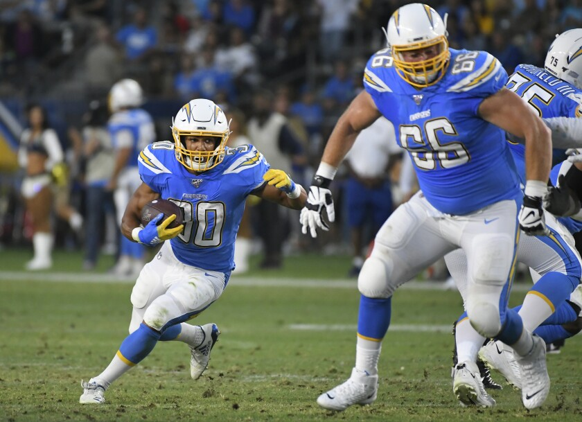 Chargers running back Austin Ekeler follows lineman Dan Feeney during a preseason game against the Seattle Seahawks on Saturday.