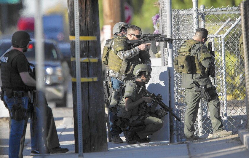 SWAT officers search near Victoria Elementary School for those involved in the attack at the Inland Regional Center in San Bernardino. Witnesses initially reported that three shooters were involved.