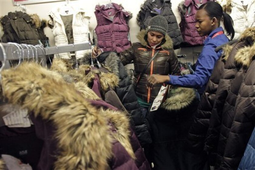 In this photo taken Dec. 18, 2010, a customer service associate helps Kenia Alvarez, center, of the Bronx borough of New York, choose a coat at the J.C. Penney store at the Manhattan Mall in New York. U.S. retailers are reporting surprisingly weak December revenue after a strong November pulled forward holiday spending and a blizzard in the Northeast took a bite out of sales after Christmas. (AP Photo/Mary Altaffer)