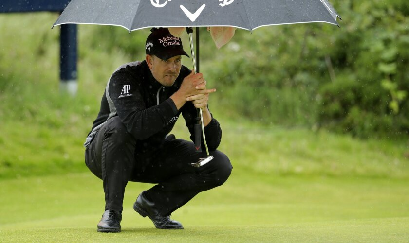 Henrik Stenson of Sweden looks at his putt on the 9th green as he holds an umbrella during the second round of the British Open Golf Championship at the Royal Troon Golf Club in Troon, Scotland, Friday, July 15, 2016. (AP Photo/Matt Dunham)