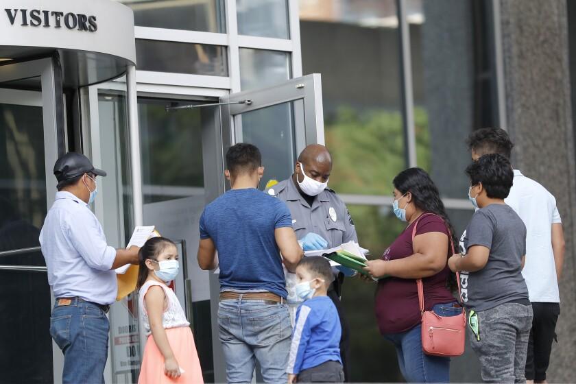 Un agente de seguridad, al centro, revisa los papeles de unas personas frente a un edificio federal