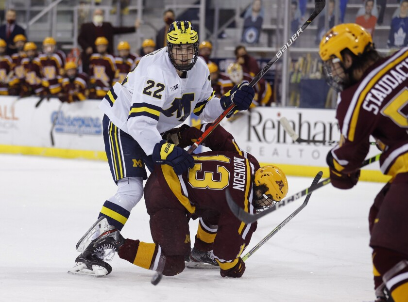 FILE - In this Dec. 8, 2020, file photo, Michigan's Owen Power (22) watches the puck while working against Minnesota's Cullen Munson (13) during an NCAA hockey game in Ann Arbor, Mich. Ann Arbor became a must-stop on the scouting trail because of a buzz-worthy Wolverines lineup featuring a trio of highly touted freshmen in defenseman Owen Power, and forwards Kent Johnson and Mathew Beniers. (AP Photo/Al Goldis, File)