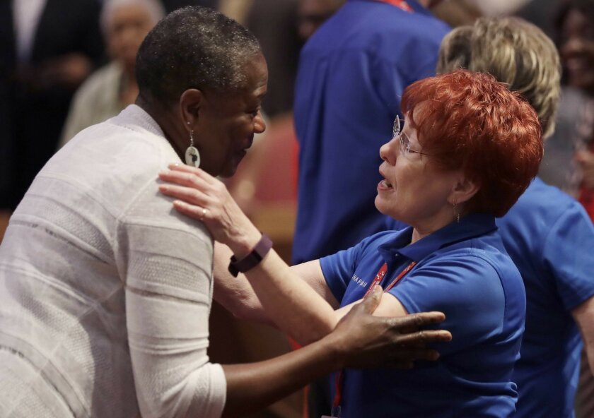 A chaplain, right, talks with a woman before a service at the Potter's House, Sunday, July 10, 2016, in Dallas that included a memorial to the five Dallas police officers killed last week as well as a town hall meeting to discuss recent shootings. (AP Photo/Eric Gay)