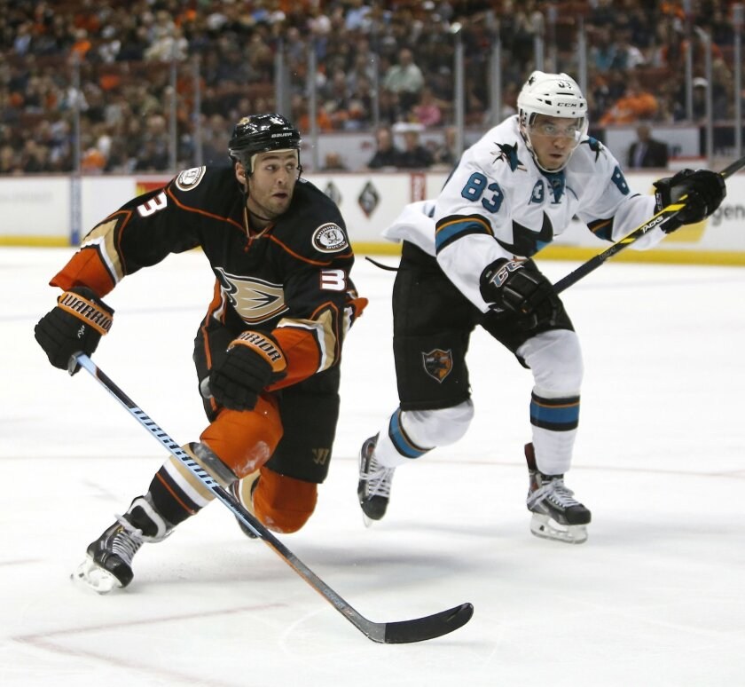 Anaheim Ducks defenseman Clayton Stoner, left, and San Jose Sharks left wing Matt Nieto race to the puck during the third period of a preseason NHL hockey game in Anaheim, Calif., on Saturday, Oct. 4, 2014. The Ducks won 2-1 in overtime. (AP Photo/Christine Cotter)