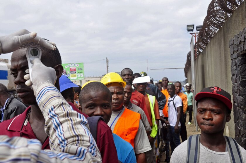 Workers have their temperature taken before entering the Freeport area, an important commercial port facility, Monrovia, Liberia, Monday, Aug. 11, 2014. Experts say fear and misunderstanding of Ebola have led many to ignore medical advice, fueling the disease's spread. (AP Photo/Abbas Dulleh)