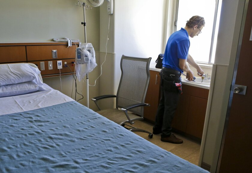Tyler Locke of Water Saver Solutions checks the water pressure of a sink at Tri-City Medical Center in Oceanside.