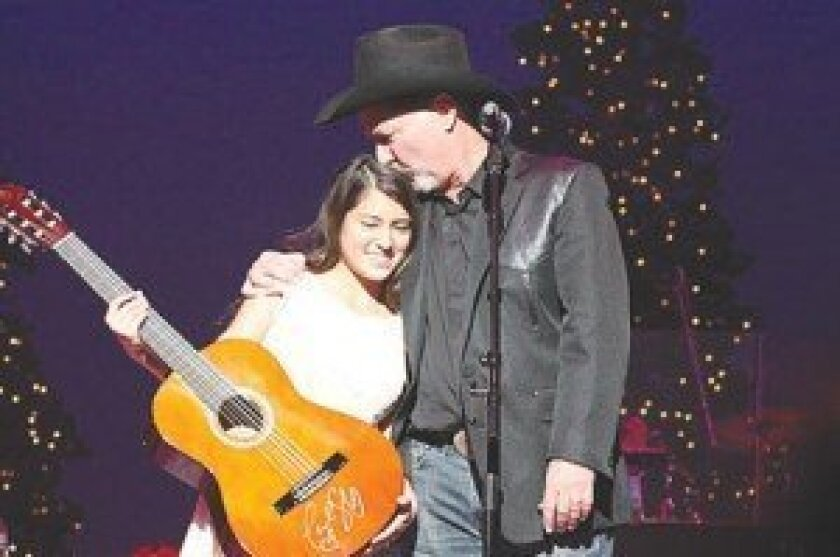 """Kirsten Blackburn receives a Christmas surprise from Steve Vaus, as he returns the guitar she donated to the """"Carols by Candlelight"""" auction. The guitar was returned to her by the auction winners. Photo by Sherri Cortez"""