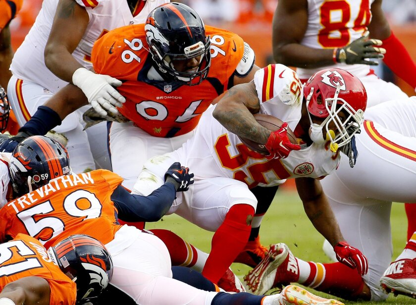 Kansas City Chiefs running back Charcandrick West (35) is stopped by Denver Broncos defensive end Vance Walker (96) during the first half of an NFL football game, Sunday, Nov. 15, 2015, in Denver. (AP Photo/Jack Dempsey)