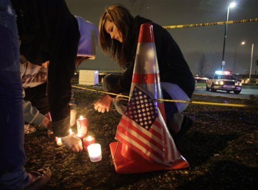 Janai Roberts, 17, lights a candle in front of a growing display of flowers, candles, and messages of sympathy in front of the Forza Coffee Company in Parkland, Wash., Monday, Nov. 30, 2009, where four Lakewood Police Officers were fatally shot Sunday morning as they sat in the coffee shop. (AP Photo/Ted S. Warren)