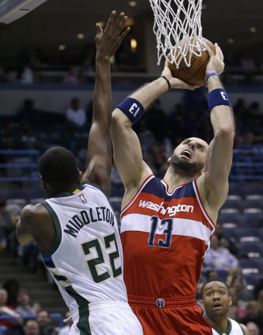 Washington Wizards' Marcin Gortat (13) goes up for a shot against Milwaukee Bucks' Khris Middleton (22) during an NBA basketball game Thursday, Feb. 11, 2016, in Milwaukee. (AP Photo/Aaron Gash)