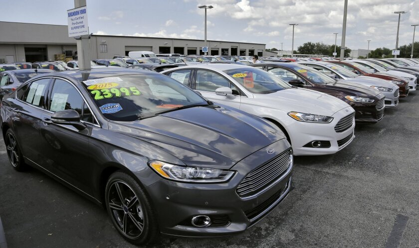 A car salesman works the telephone while searching through inventory at the certified used car lot at Brandon Ford in Brandon, Fla. on Tuesday, Nov. 3, 2015. Sales of new cars and trucks rose by double-digit percentages at most major automakers in October, and companies are raising their expectatio
