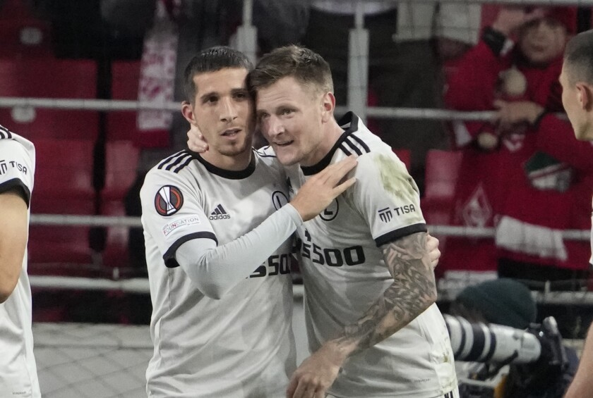 Legia's Lirim Kastrati, left, celebrates after scoring his side's opening goal during the Europa League Group C soccer match between Spartak Moscow and Legia Warsaw at the Otkritie Arena, in Moscow, Russia, Wednesday, Sept. 15, 2021. (AP Photo/Pavel Golovkin)