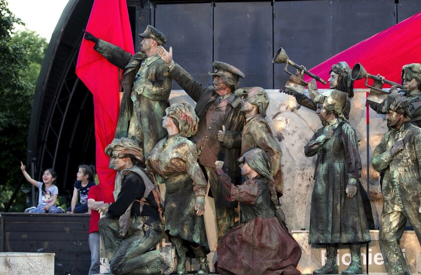 In this May 22, 2016, picture actors perform in Lenin's Arc play, staged by the Masca Theatre in Bucharest, Romania. Romanians relive the horrors of communism in a play featuring Lenin and Stalin, set to patriotic songs of that era, played by actors who mime their roles, the hour-long performance i