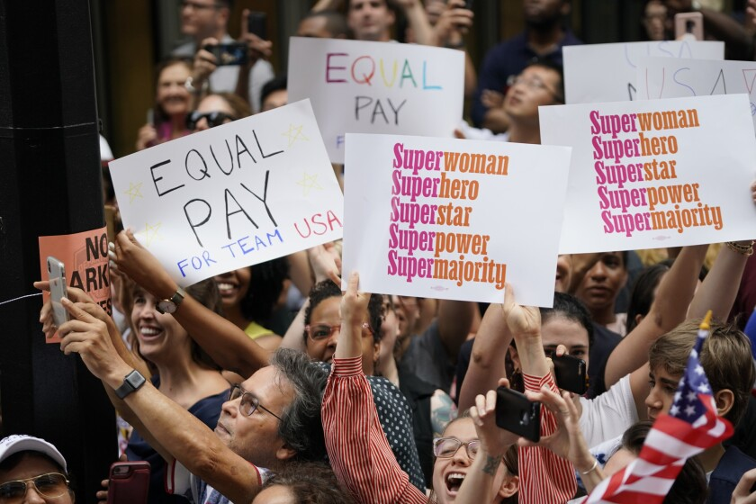 Equal Pay signs seen during the Ticker Tape Parade for the U.S. Women's National Team as they celebr