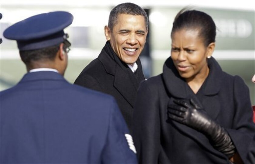 President Barack Obama and first lady Michelle Obama greet people as they step off Air Force One at Andrews Air Force Base, Md., Monday, Jan. 4, 2010, after spending the holidays in Hawaii. (AP Photo/Alex Brandon)