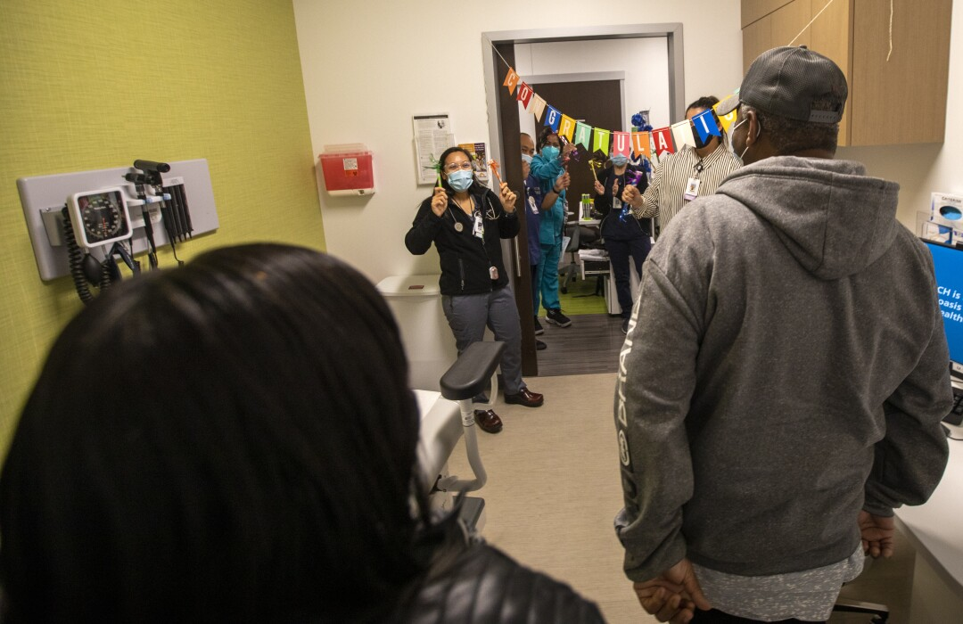 Richard and Audrey Perry walk into a clinic to a warm reception.