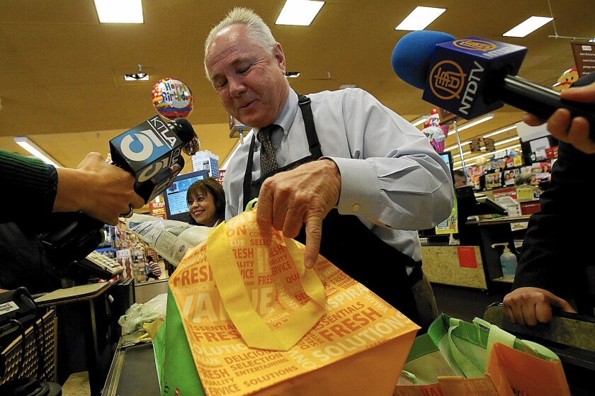 Outgoing Los Angeles City Councilman Tom LaBonge bags groceries at a Pavilions in December 2013. The two spots in the runoff race to replace him are still undecided.