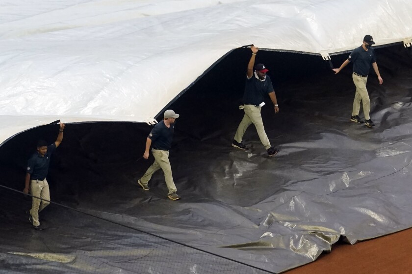 Members of the Atlanta Braves grounds crew work to cover the infield at Truist Park
